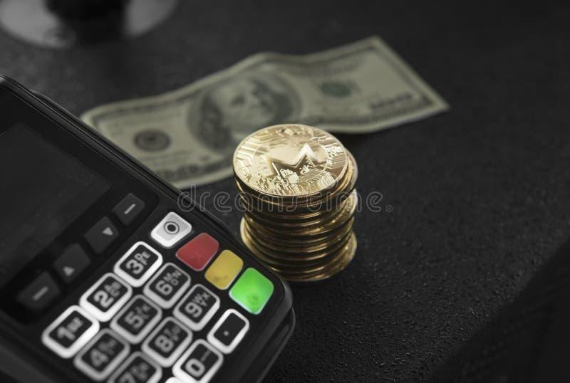 Uma pilha de moedas de Monero do ouro e de terminal da posição com uma cédula hindred do dólar em um fundo Moneros Cryptocurrency imagem de stock