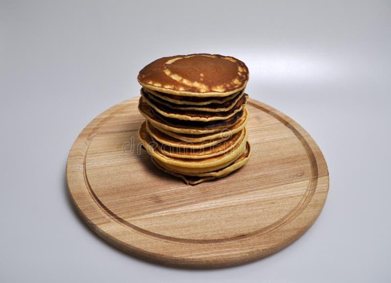 Uma pilha de panquecas douradas redondas em um suporte de madeira imagem de stock