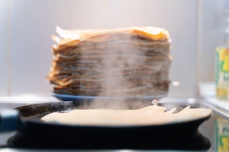 Uma pilha de panquecas fritadas pré-feitos as panquecas são fritadas em uma frigideira preta foto de stock