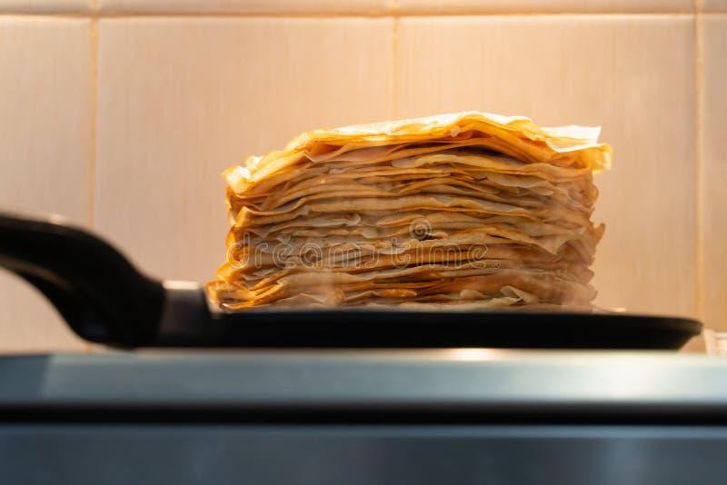 Uma pilha de panquecas fritadas pré-feitos as panquecas são fritadas em uma frigideira preta foto de stock royalty free