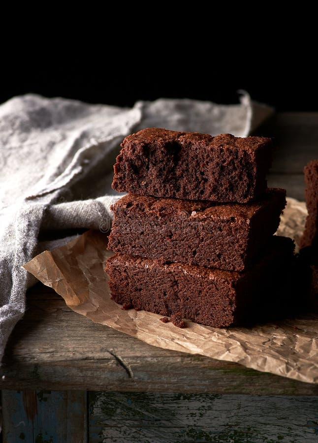 Uma pilha de partes quadradas cozidas de bolo da brownie do chocolate no papel de pergaminho marrom fotos de stock
