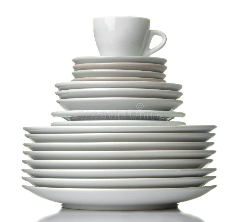 Uma pilha de pratos dinnerware placas e copo em um fundo isolado branco Close-up imagens de stock