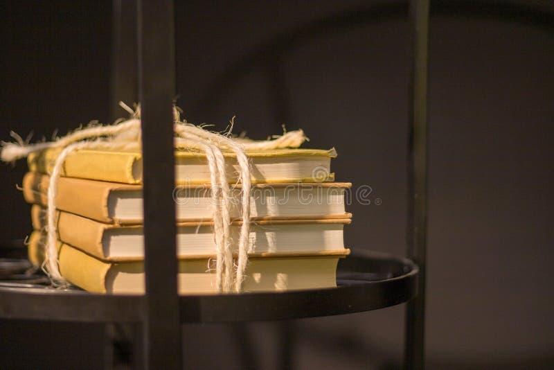 Uma pilha de quatro livros amarrados com uma corda e o encontro em uma prateleira em uma tabela de cabeceira de madeira imagem de stock royalty free