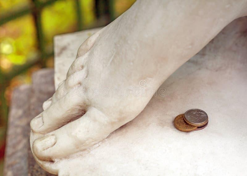 Uma pilha de quatro moedas do russo que encontram-se ao lado dos pés de uma estátua de mármore antiga com um fundo borrado imagens de stock royalty free