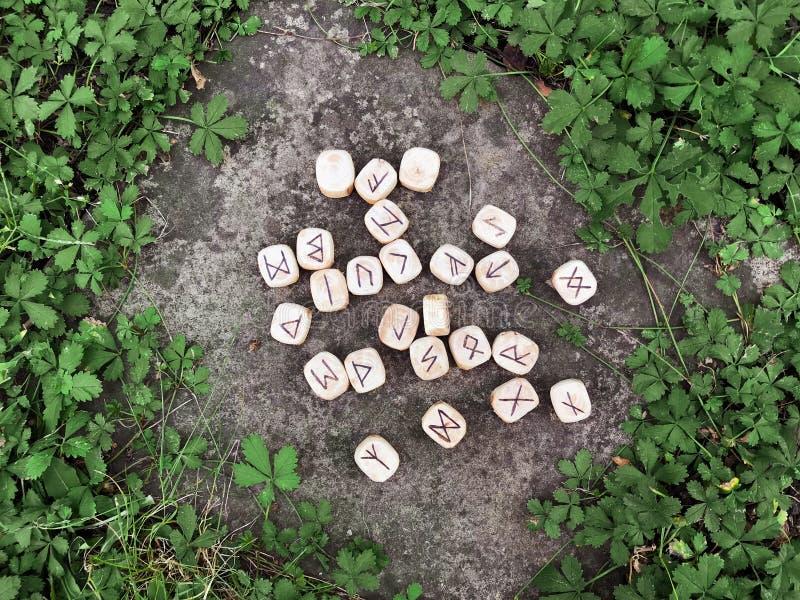 Uma pilha de runas de madeira em runas de madeira da floresta encontra-se em um fundo da rocha na grama verde As runas são cortad imagem de stock royalty free