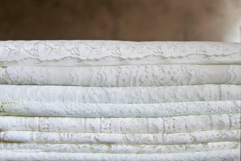Uma pilha de telas de matéria têxtil tradicionais delicadas do laço em um teste padrão natural na cor branca imagem de stock royalty free