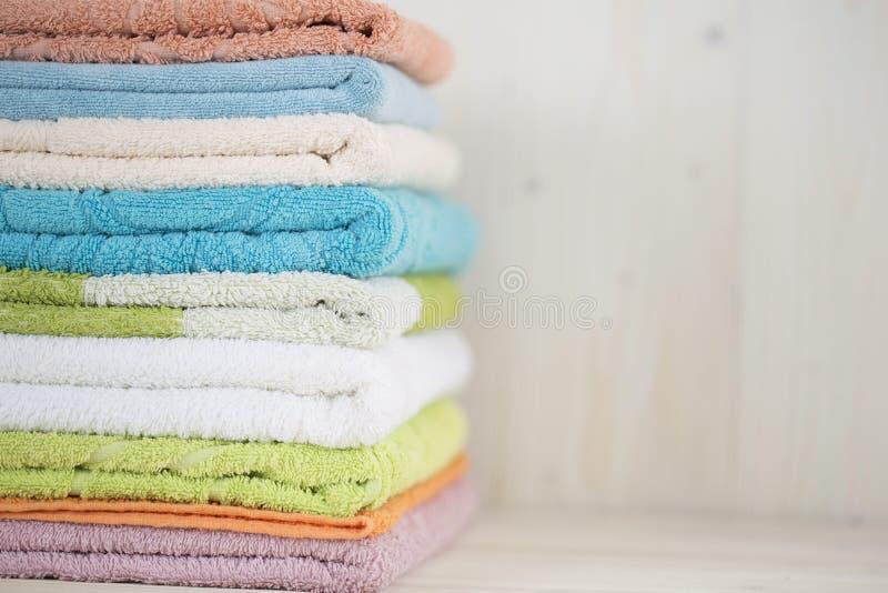 Uma pilha de toalhas multi-coloridas limpas em uma superfície de madeira fotos de stock