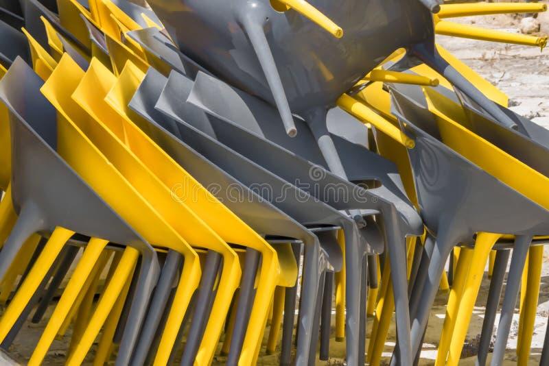 Uma pilha do fundo plástico amarelo e cinzento brilhante das cadeiras imagem de stock royalty free