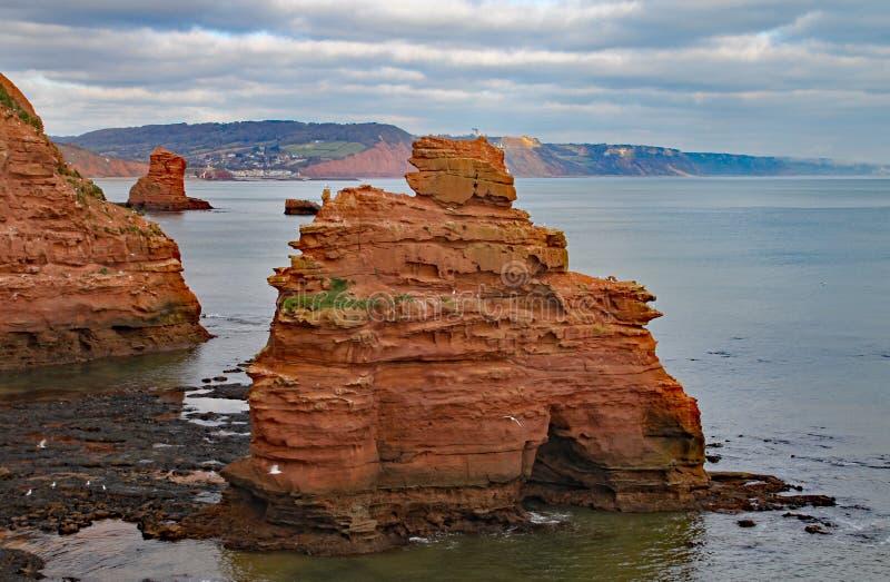 Uma pilha do mar do arenito na baía perto de Sidmouth, Devon de Ladram Peça do trajeto litoral ocidental sul Sidmouth é visível n foto de stock royalty free