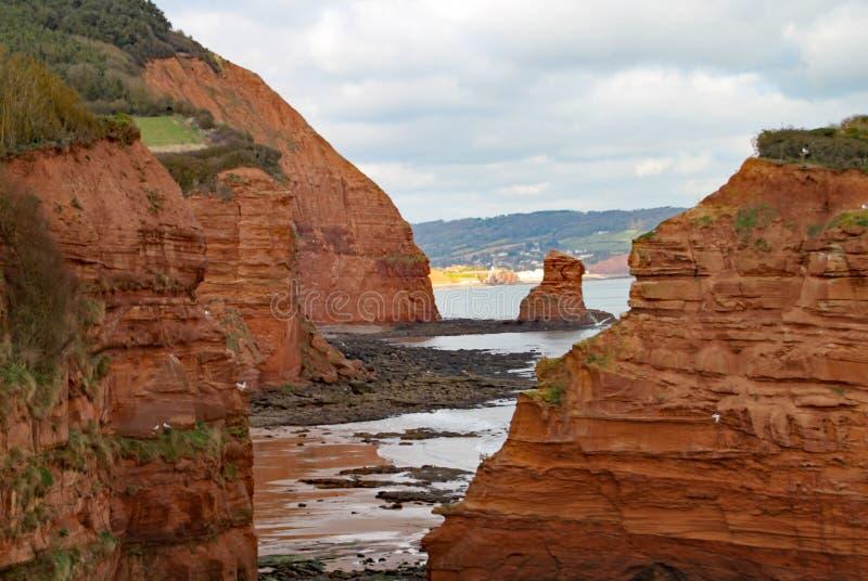 Uma pilha do mar do arenito na baía perto de Sidmouth, Devon de Ladram Peça do trajeto litoral ocidental sul Sidmouth é visível n fotos de stock royalty free