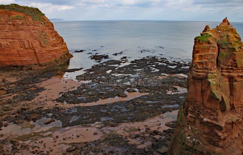 Uma pilha do mar do arenito na baía perto de Sidmouth, Devon de Ladram Peça do trajeto litoral ocidental sul imagem de stock royalty free