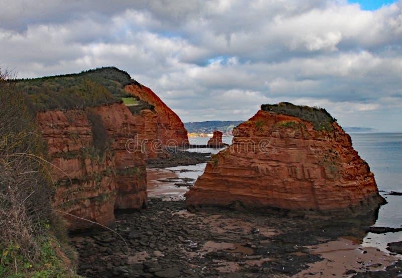Uma pilha do mar do arenito do sandA na baía perto de Sidmouth, Devon de Ladram Peça do trajeto litoral ocidental sul Sidmouth é  imagens de stock