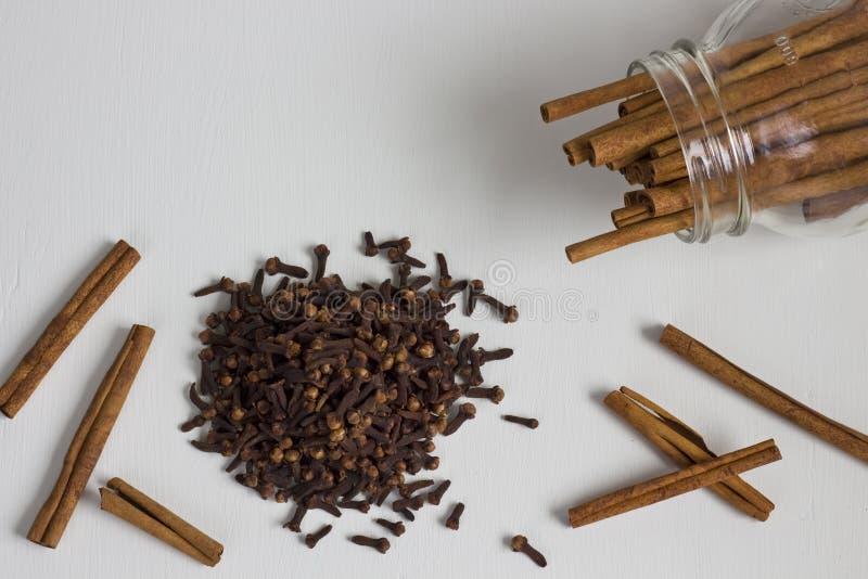 Uma pilha dos cravos-da-índia e das varas de canela foto de stock