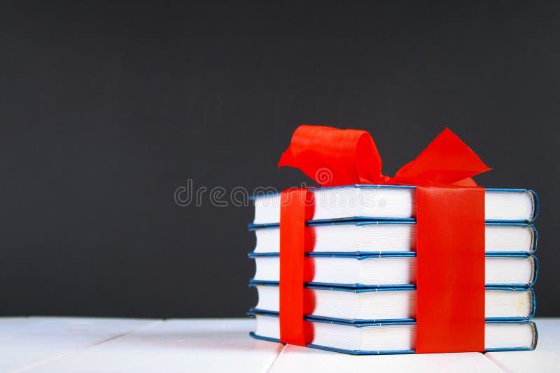 Uma pilha dos livros amarrados com uma fita vermelha em uma tabela de madeira branca Um presente no fundo de um quadro imagens de stock royalty free