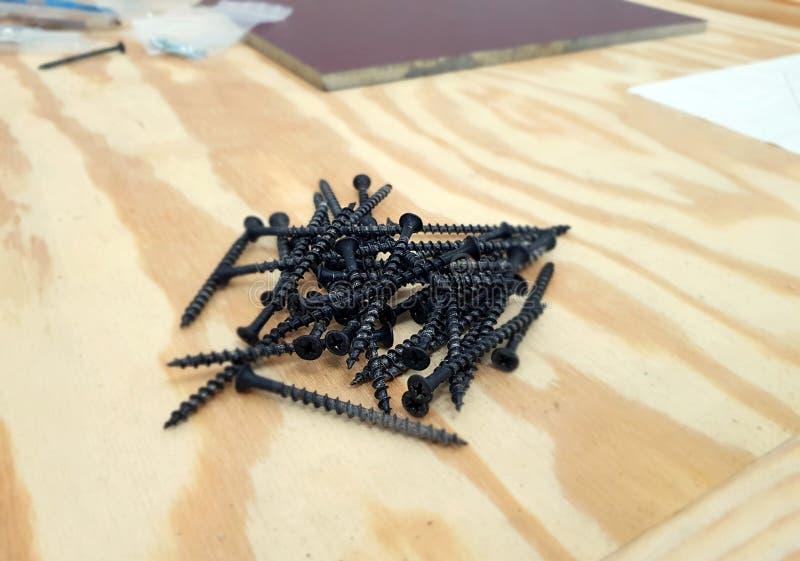 Uma pilha dos parafusos de batida do auto preto isolados fotografia de stock