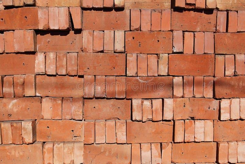 Uma pilha organizada dos tijolos vermelhos fracos empilhados sobre se fotos de stock