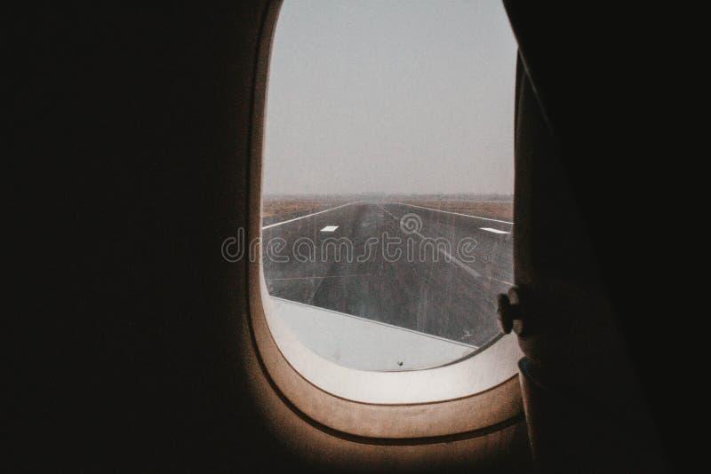 Uma pista de decolagem do avião disparada de uma janela do avião imagem de stock