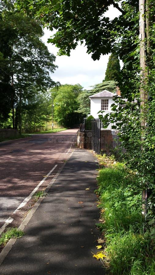 Uma pista inglesa bonita do campo com casa branca e a parede de pedra imagens de stock