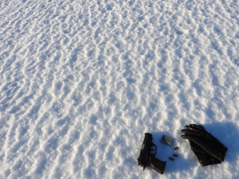 Uma pistola e balas de 9mm com as luvas pretas dispersadas na neve imagens de stock royalty free