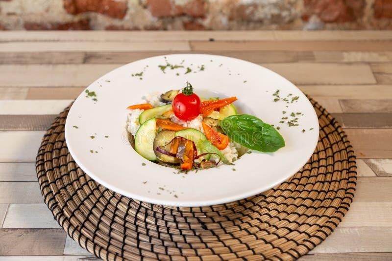 Uma placa branca com arroz e os legumes frescos fotos de stock royalty free