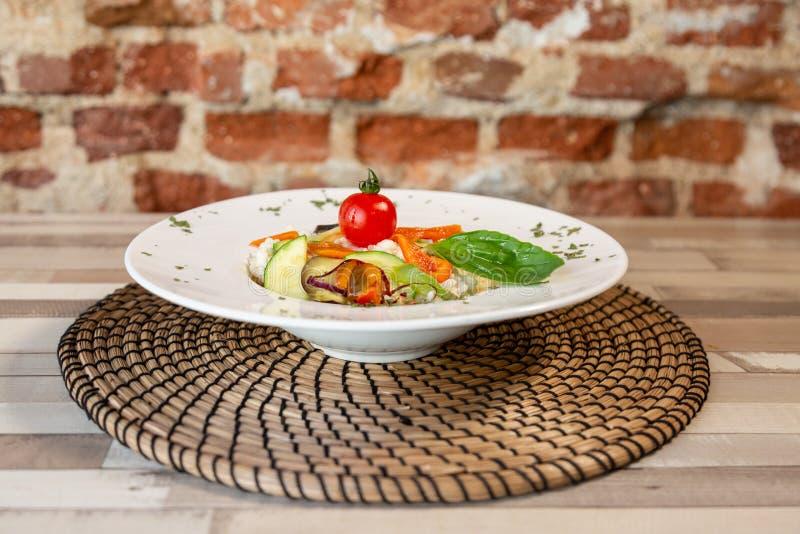 Uma placa branca com arroz e os legumes frescos imagens de stock royalty free