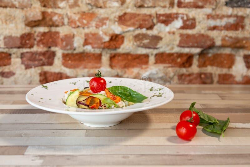 Uma placa branca com arroz e os legumes frescos Alimentos frescos do vegetariano Guarnição com os tomates dos oréganos e de cerej foto de stock royalty free