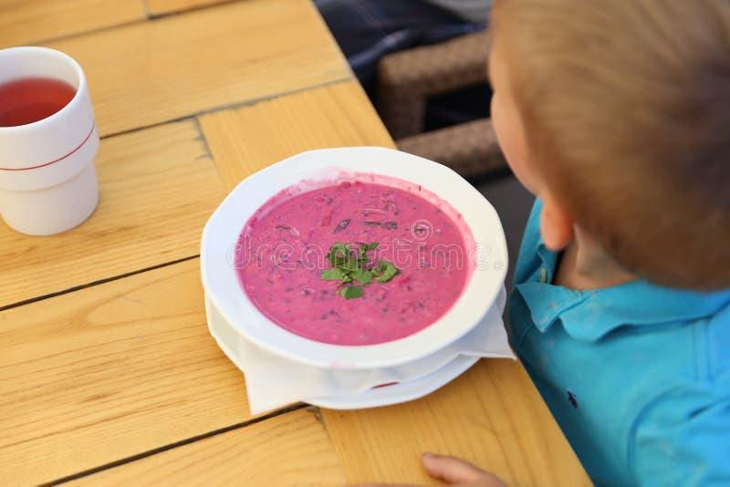 Uma placa branca com sopa grossa cor-de-rosa na frente de um menino da criança imagem de stock