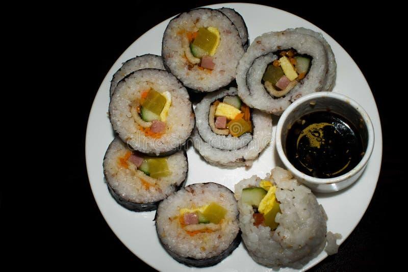 Uma placa branca completamente do sushi rolado isolado em um fundo preto imagem de stock royalty free