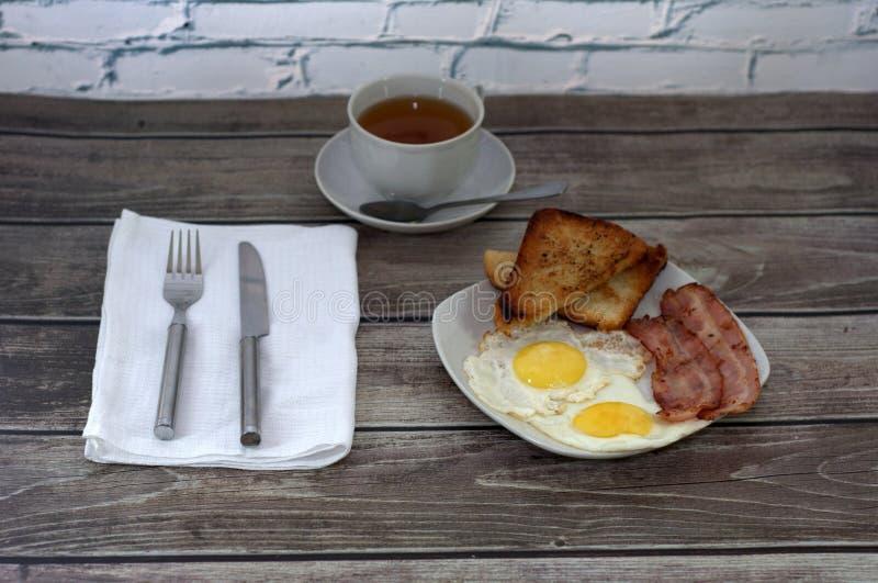 Uma placa cerâmica branca com dois ovos fritos, brindes e bacon está na tabela, ao lado de uma forquilha e de uma faca em um guar fotografia de stock