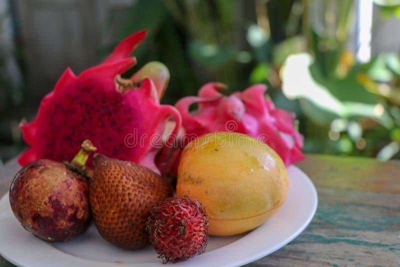 Uma placa com frutos tropicais asiáticos como um deserto ou um fruto simples do dragão do prato, manga, fruto da serpente fotos de stock