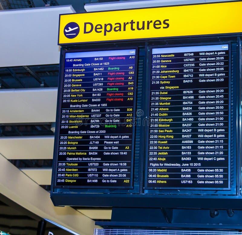 Uma placa da partida do voo que mostra os voos internacionais do longo-curso que saem do aeroporto do ` s Heathrow de Londres foto de stock
