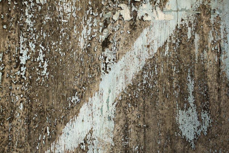 Uma placa de madeira cinzenta velha com quebras e descascamento da pintura azul Linha diagonal Textura da superfície áspera imagens de stock royalty free