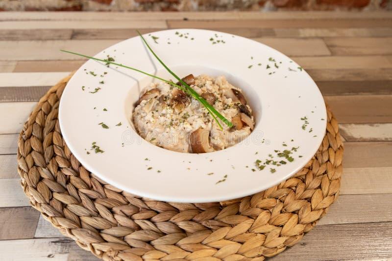 Uma placa do risoto do cogumelo em uma tabela de madeira fotos de stock royalty free