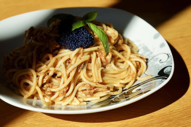 Uma placa dos espaguetes com o caviar na parte superior imagens de stock royalty free