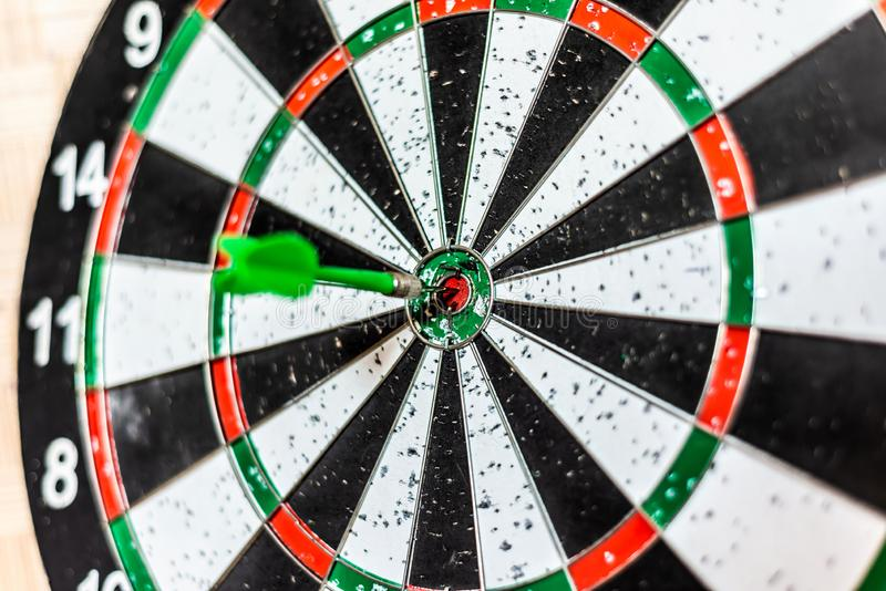 Uma placa redonda para jogar dardos perto acima, um dardo verde bateu o alvo imagens de stock royalty free
