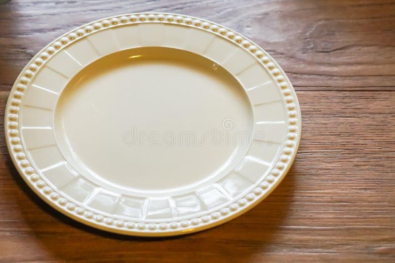 Uma placa vazia é colocada em uma tabela de madeira fotografia de stock royalty free