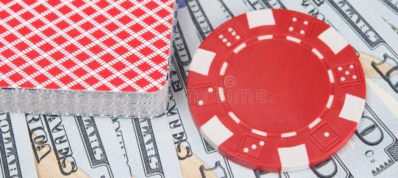 Uma plataforma de cartões para jogar no casino e em uma microplaqueta para apostar no fundo das notas de dólar fotografia de stock royalty free