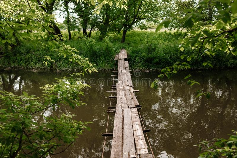 Uma ponte de madeira pequena sobre um córrego suave em um parque verde fotos de stock