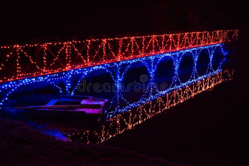 Uma ponte iluminada molda sua luz em um barco de enfileiramento fotografia de stock royalty free