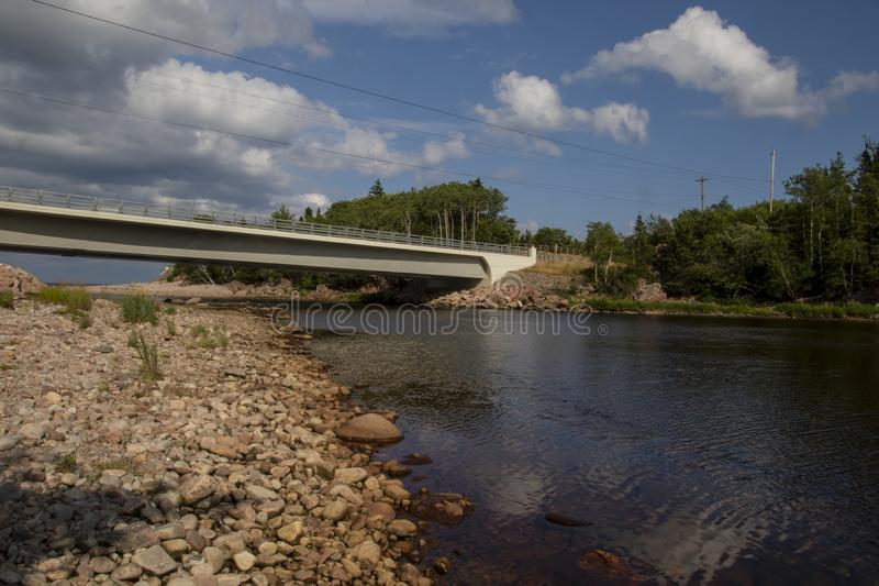 Uma ponte que vai sobre um rio com a floresta no lado do assistente imagem de stock royalty free