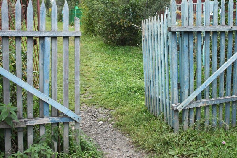 Uma porta áspera velha azul a um jardim da dacha em uma vila com terra e grama e árvores foto de stock royalty free