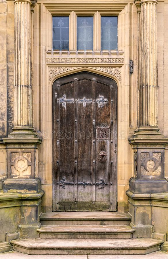 Uma porta de madeira marrom antiga com dobradiças incomuns imagens de stock royalty free
