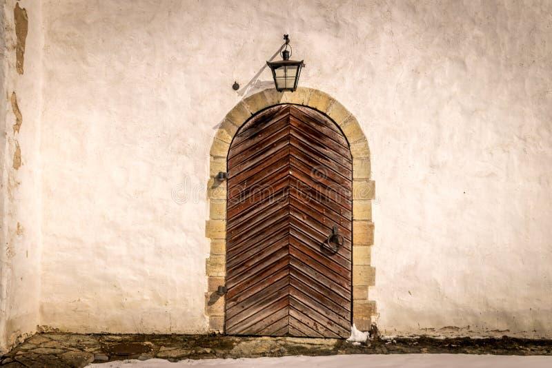 Uma porta de madeira marrom antiga com uma lâmpada de parede velha fotos de stock