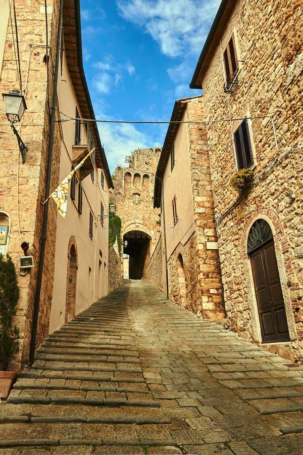 Uma porta de pedra, escadas e uma rua estreita com casas históricas imagem de stock
