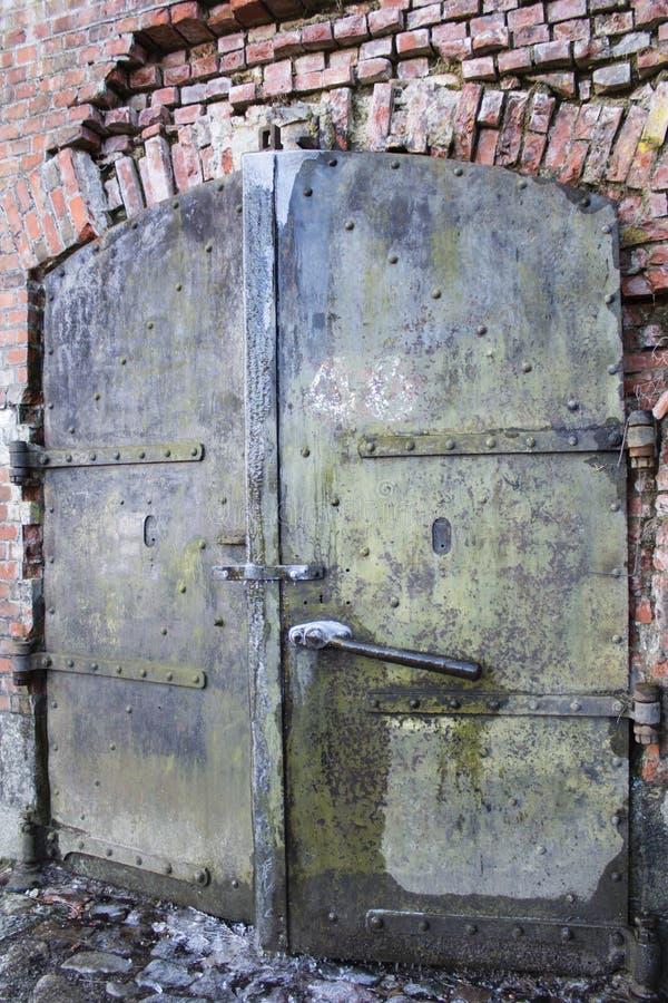 Uma porta velha do metal na parede de tijolo imagens de stock
