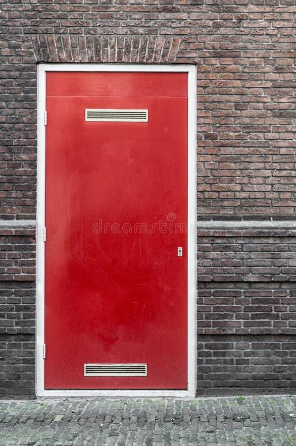 Uma porta vermelha encaixada em uma parede de pedra fotos de stock