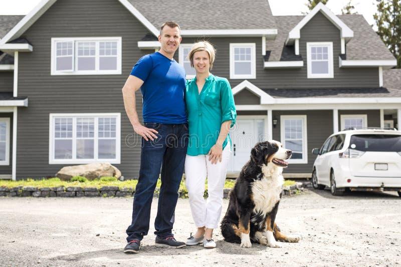 Uma posição alegre dos pares na frente da casa nova fotografia de stock