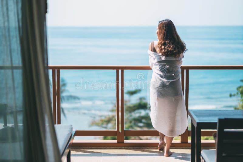 Uma posição asiática bonita da mulher e para apreciar olhar a opinião do mar fotografia de stock royalty free