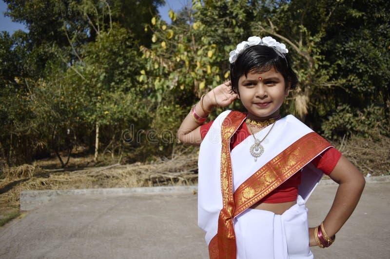 Uma posição bonito e inocente da menina da vila na frente do jardim imagem de stock royalty free