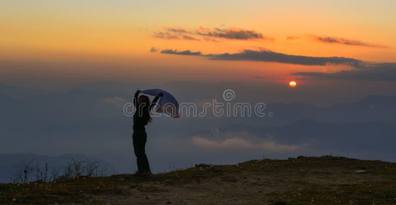 Uma posição da jovem mulher na montanha fotos de stock royalty free